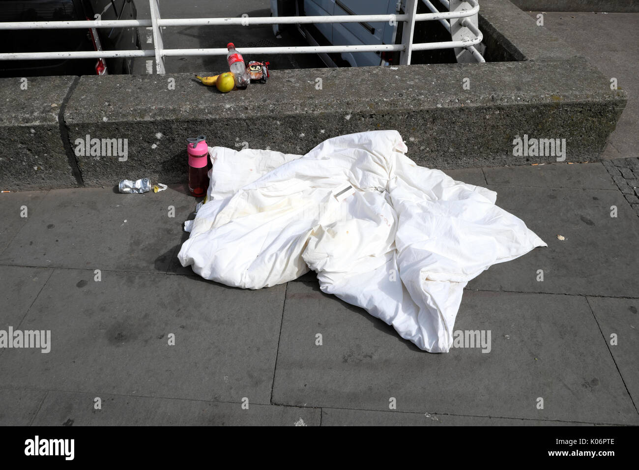 Duvet blanket, drink and food left remaining on the pavement outside the train station by a homeless person in Cardiff, Wales, UK  KATHY DEWITT - Stock Image