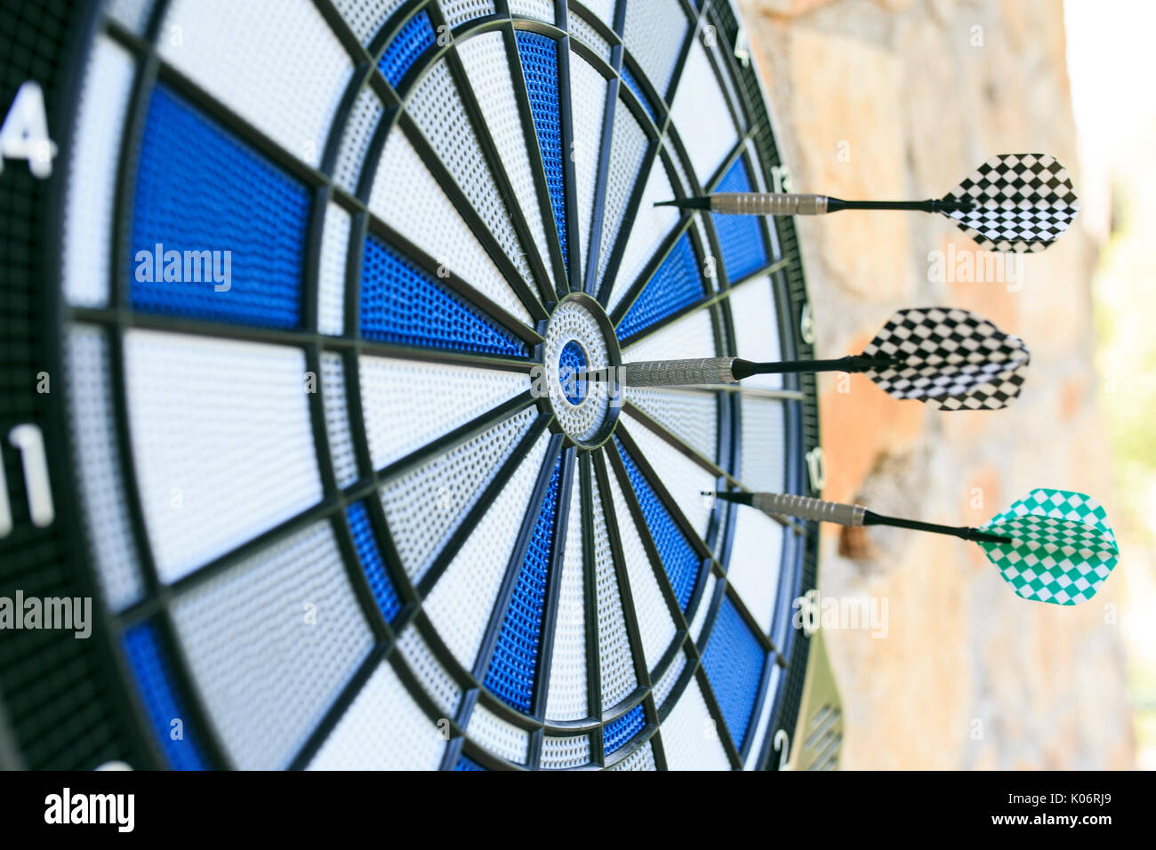 Bullseye on a wall with some darts - Stock Image
