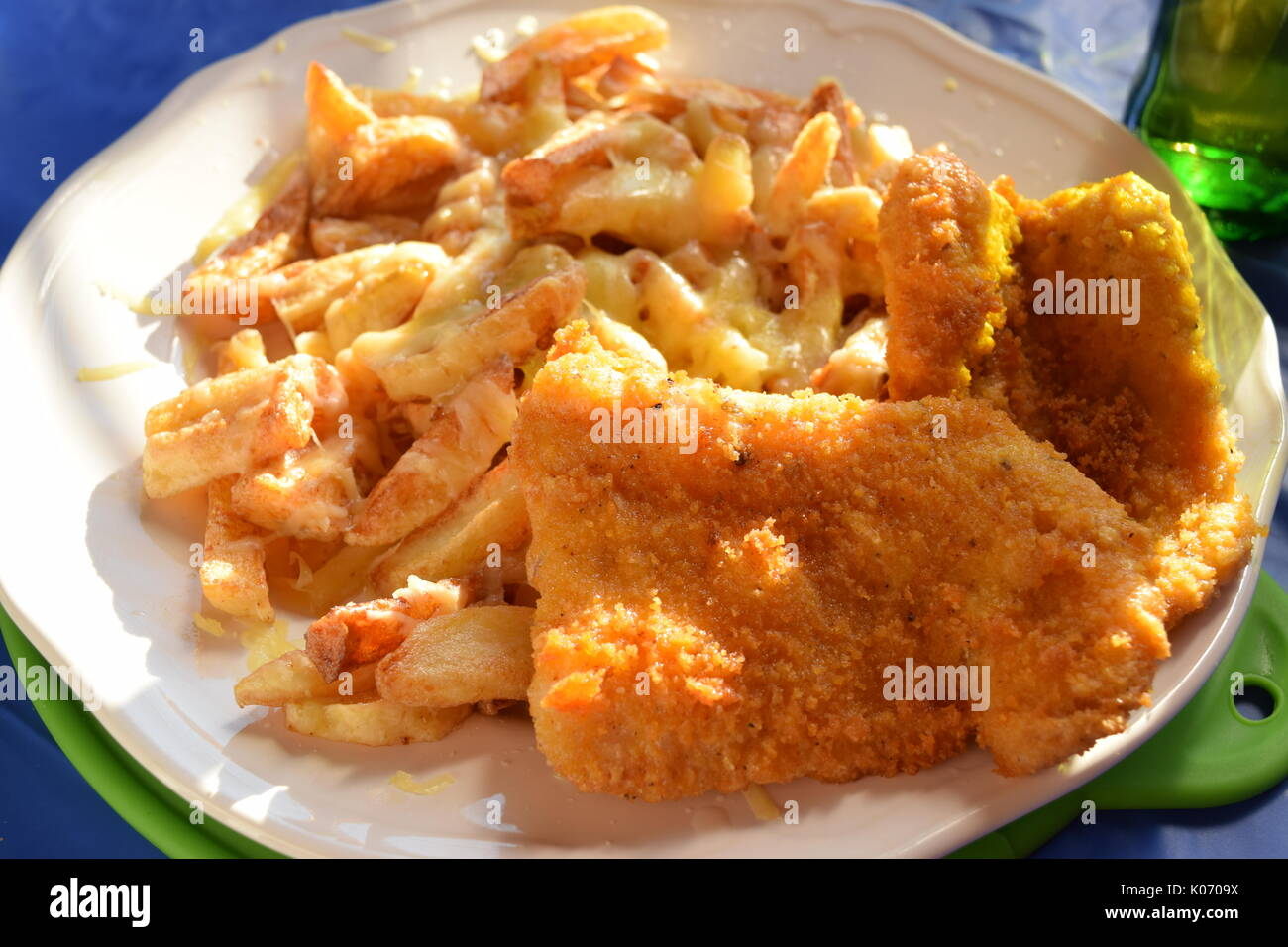 Cheesy chips and fried battered fish - Stock Image