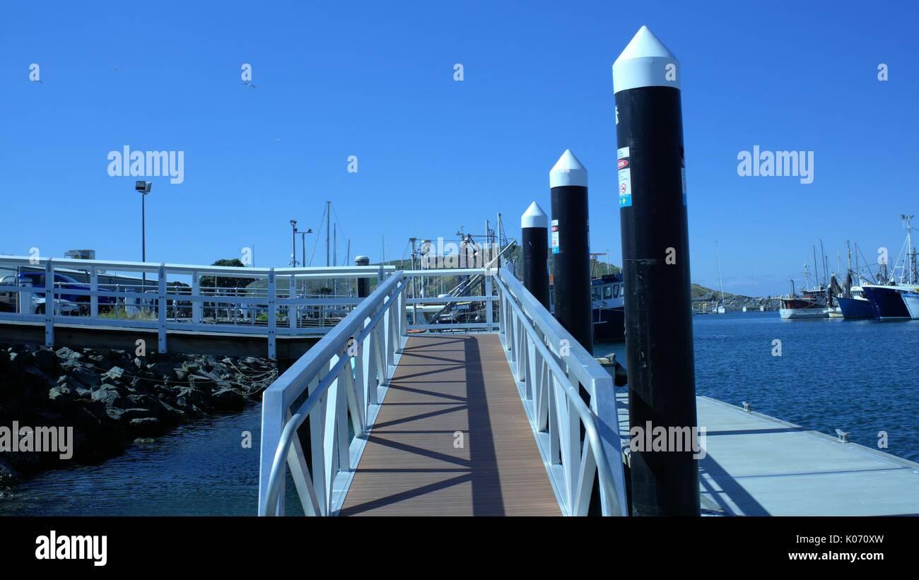 Floating pier. Pillars or pilings beside a walking ramp  or pier on sea - Stock Image
