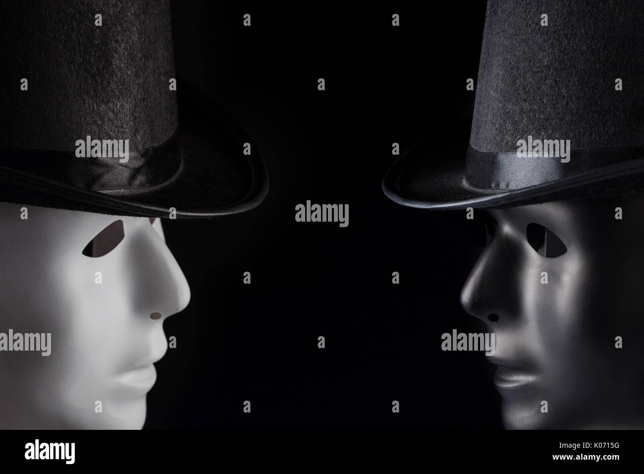 Black and white masks wearing top hats looking at each other isolated on black background with copy space. Dialogue and conversation concept - Stock Image