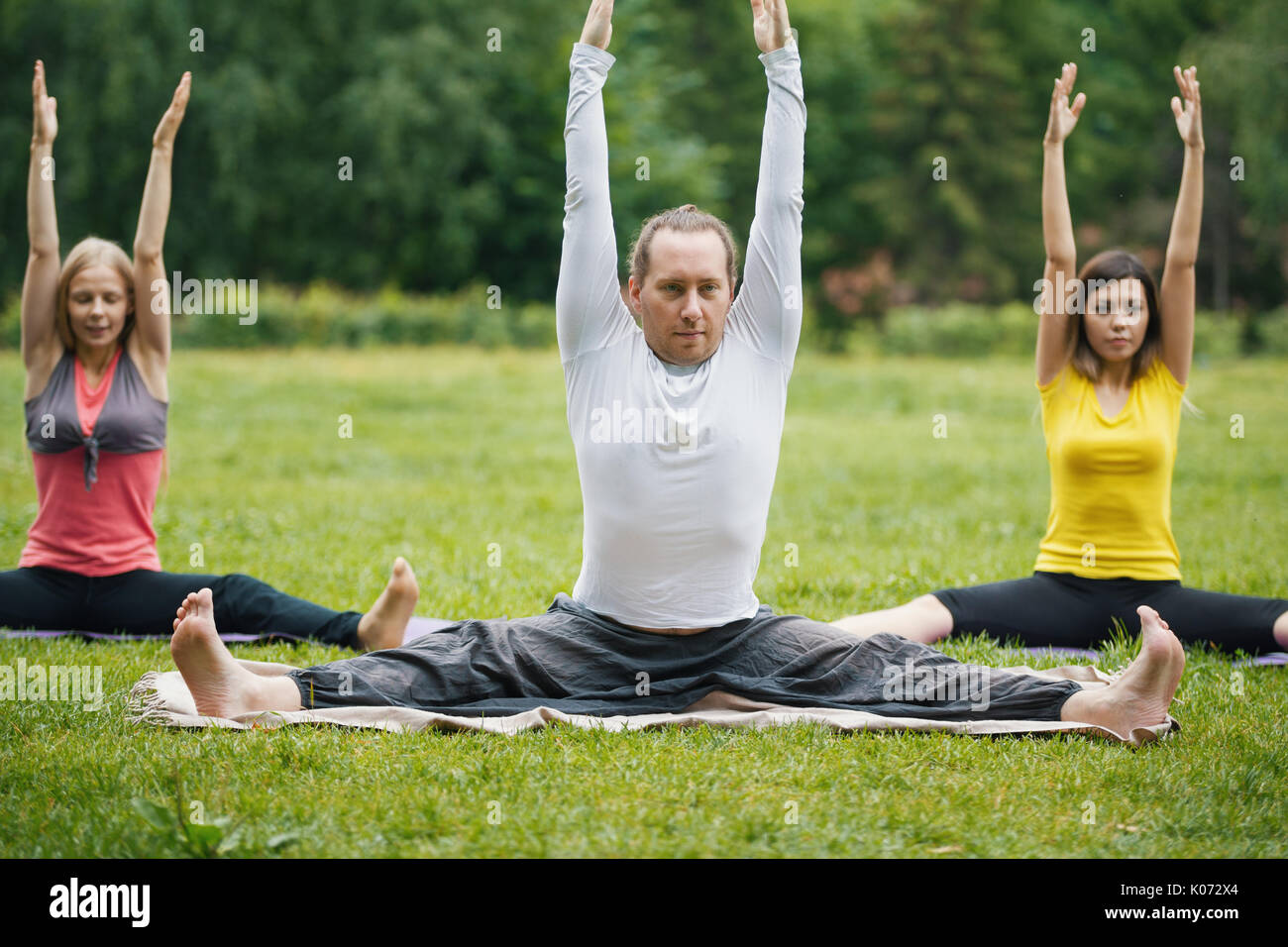 Yoga instructor shows flexibility exercise for group of girls in park - Stock Image