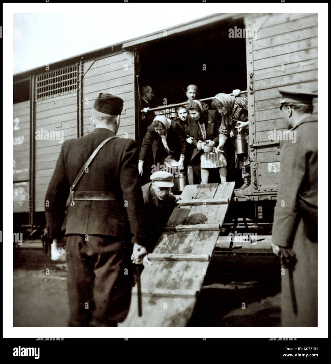 """Jewish women and children arrive by rail in bare unheated rail carriages to Auschwitz-Birkenau, a WW2 German Nazi Concentration & Extermination camp. Jewish children made up the largest group of those deported to the camp. They were usually sent there along with adults, beginning in early 1942, as part of the """"final solution of the Jewish question""""—the total destruction of the Jewish population of Europe...Auschwitz concentration camp was a network of German Nazi concentration camps and extermination camps operated by the Third Reich in Polish areas annexed by Nazi Germany during World War II. - Stock Image"""