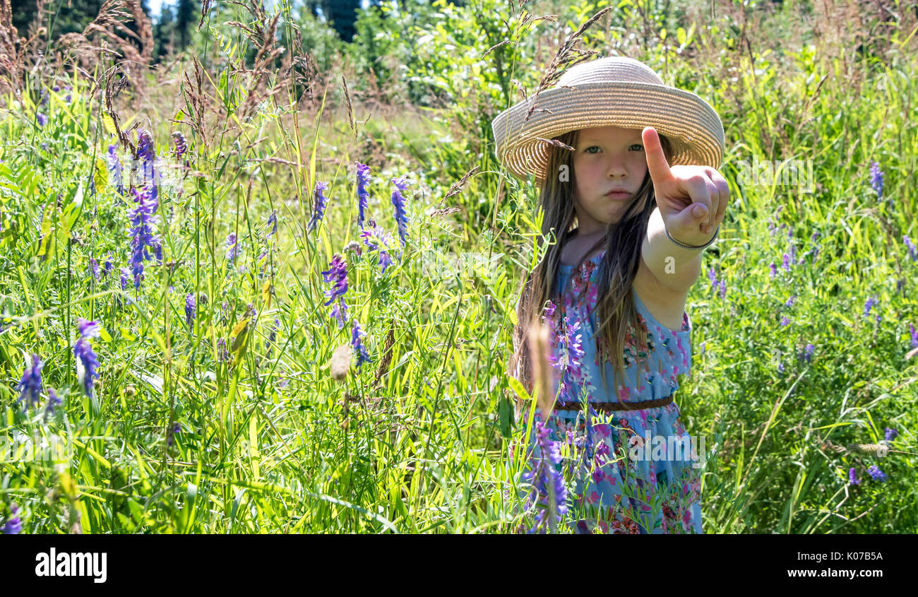 Young girl standing among flowers with her index finger extended. - Stock Image