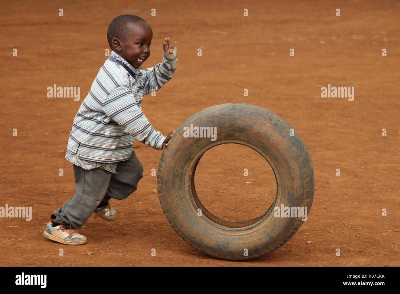 Child playing with tire, near Eldoret, Kenya, Kalingen tribal area Stock Photo
