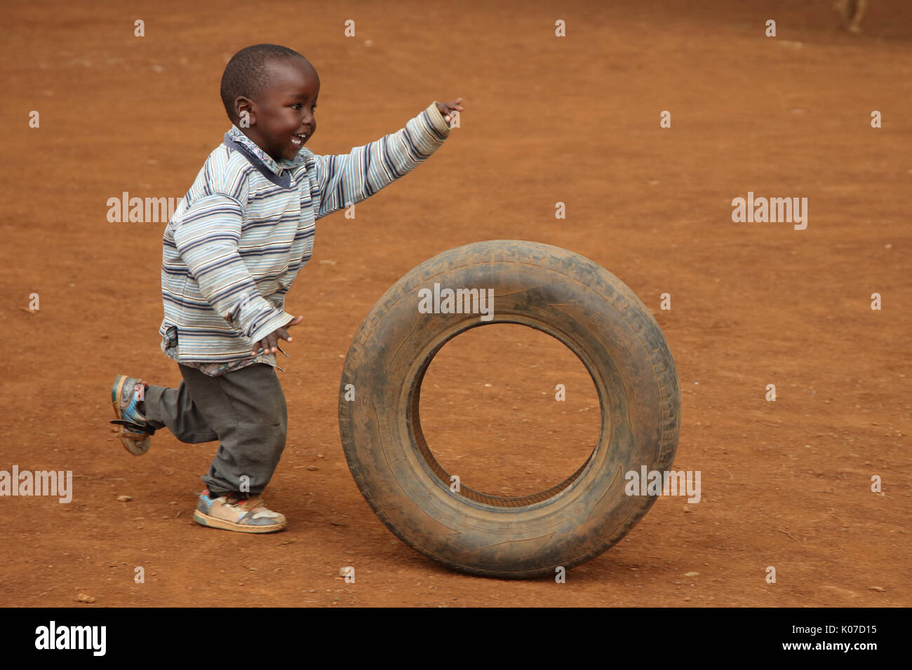 Child playing with tire, near Eldoret, Kenya, Kalingen tribal area Stock Photo