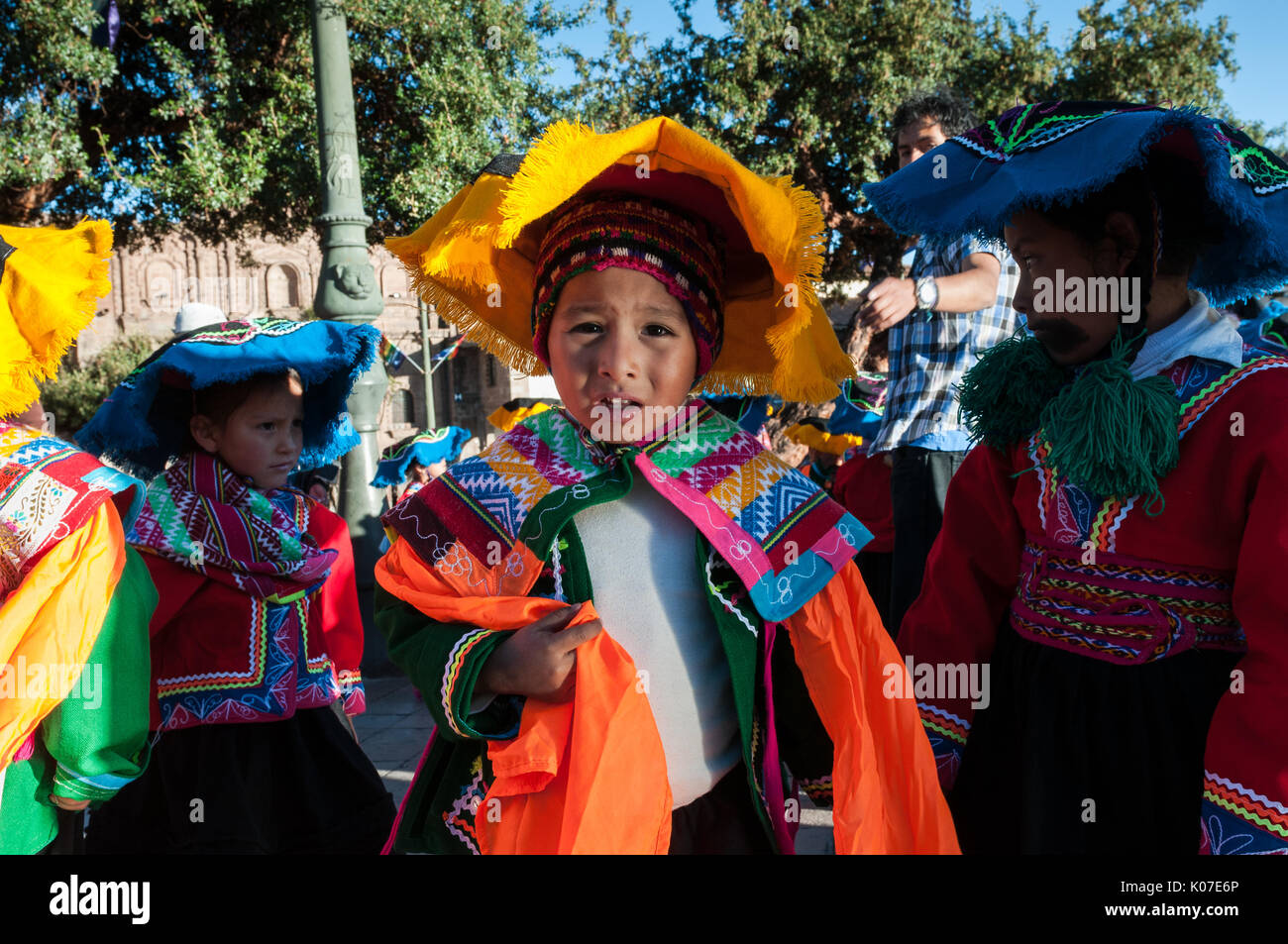 A group of children wearing Quechua ponchos and montera hats prepare for dance competition during Corpus Christi festival, Plaza de Armas, Cusco, Peru - Stock Image