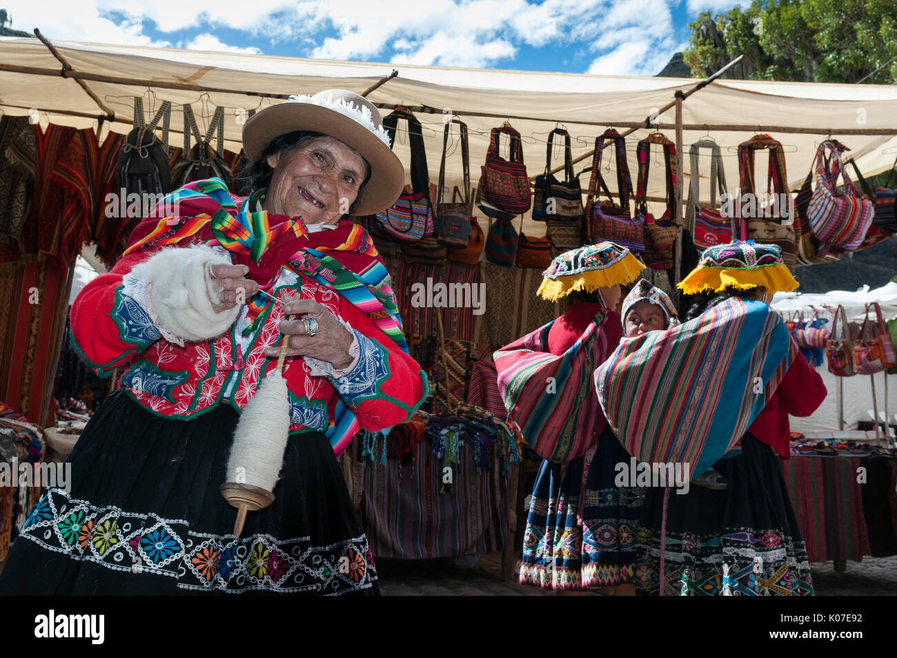 An old woman dressed in traditional Quechua clothing is hand-spinning wool into a yarn using a drop spindle in the town of Pisac near Cusco, Peru. - Stock Image