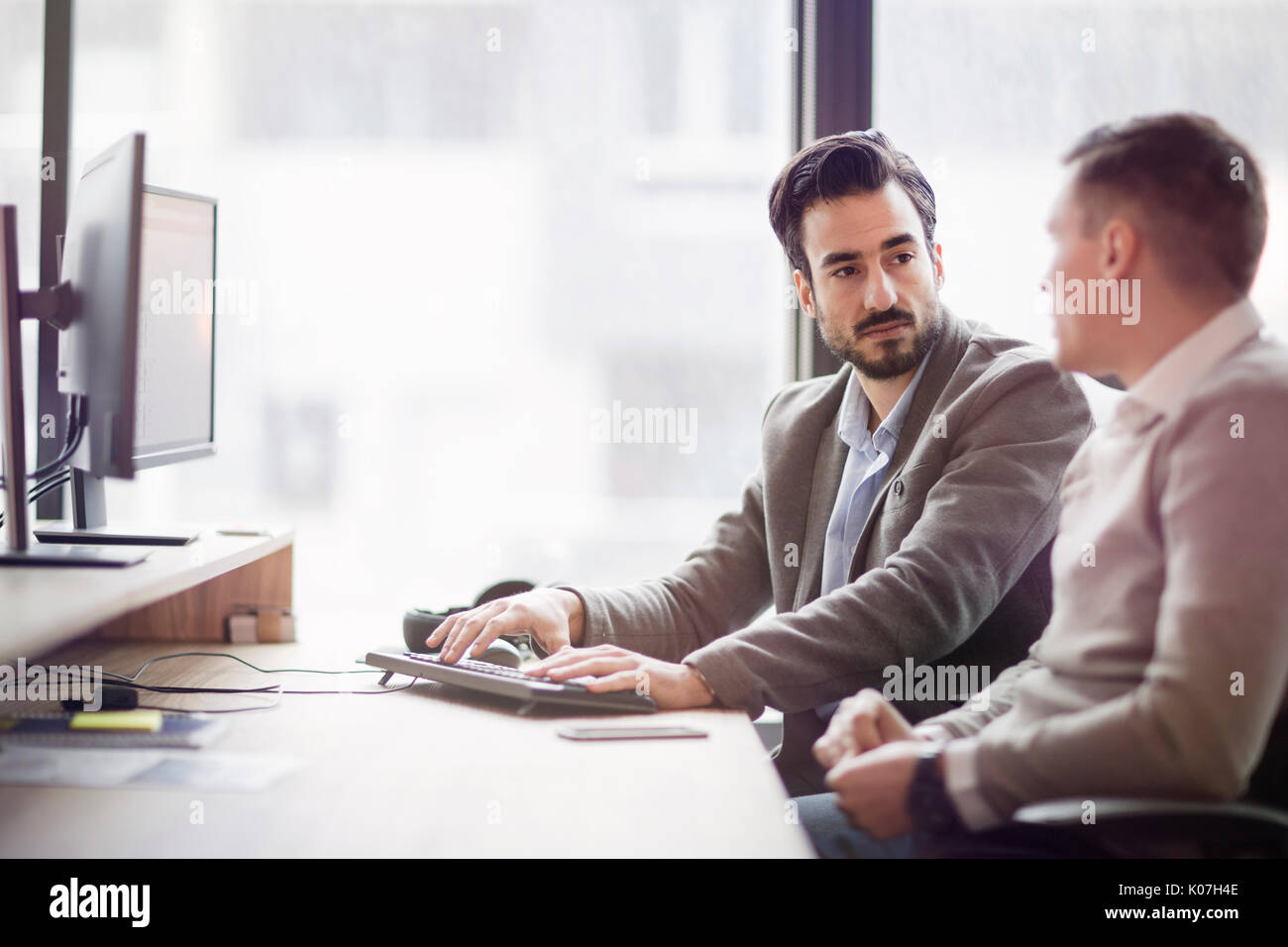Picture of two young businessmen having discussion - Stock Image