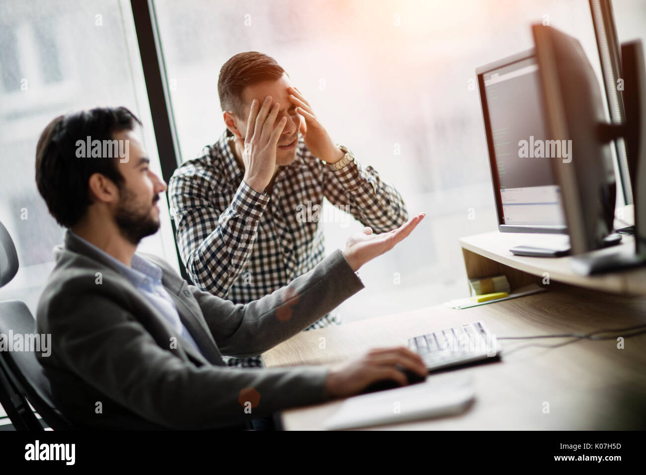 Picture of two businessmen having problems in office - Stock Image