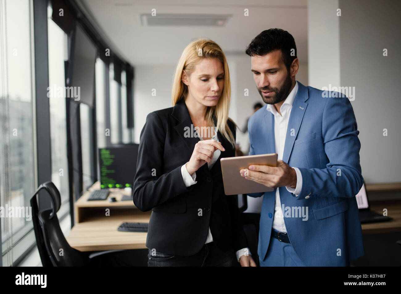 Portrait of attractive business partners using tablet - Stock Image