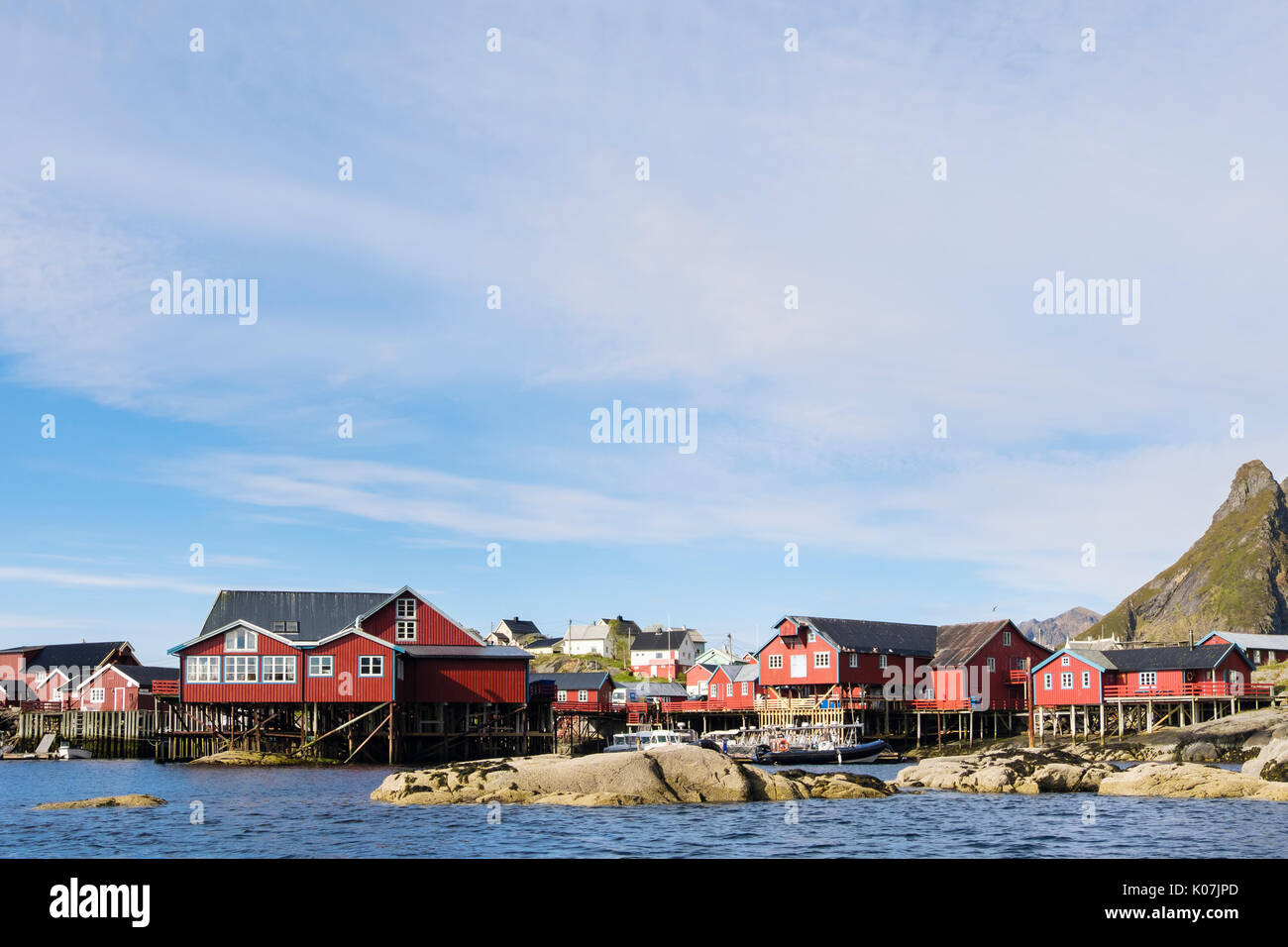 Red wooden fishermen's huts and buildings on stilts by water in fishing village of Å, Moskenes, Moskenesøya Island, Stock Photo