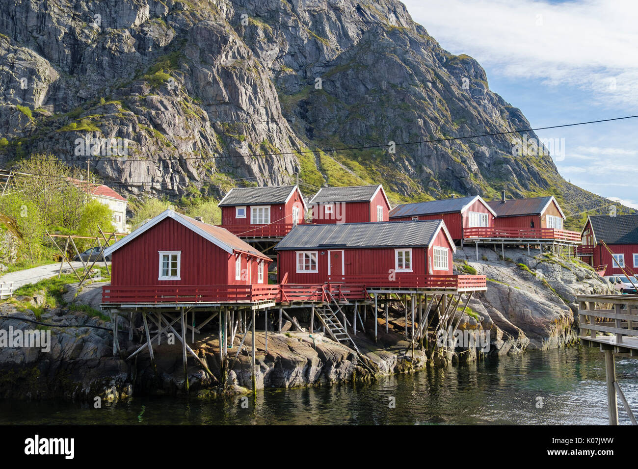 Red wooden rorbus fishermen's huts and buildings on stilts by sea in fishing village of Å, Moskenes, Moskenesøya Island, Lofoten Islands, Norway - Stock Image