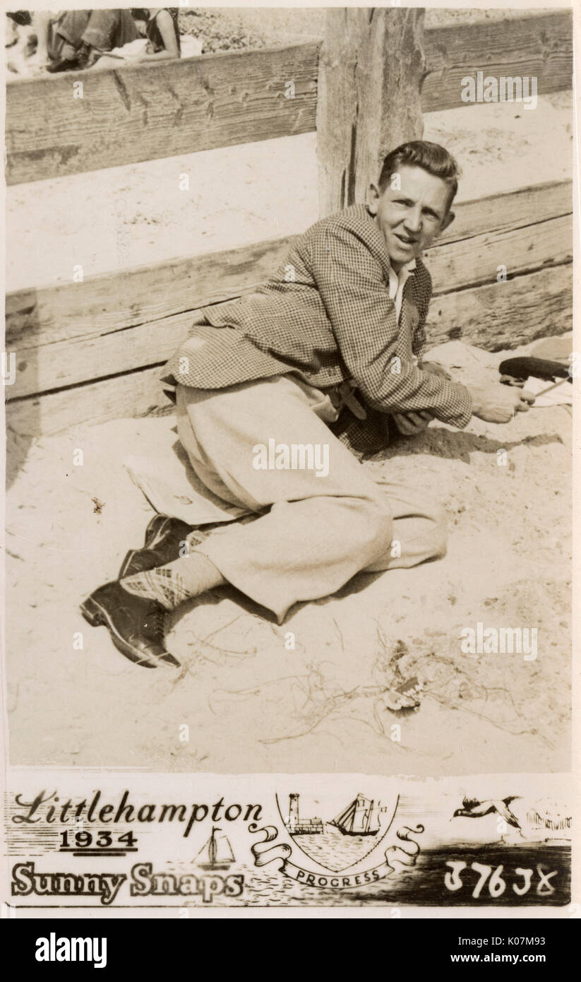 Littlehampton, West Sussex - Young man taking a breather on the beach (see: 11768188 for the previous shot featuring his Father and other half...)     Date: 1934 - Stock Image