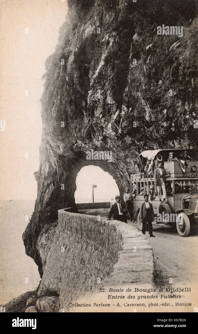 Coast road from Bougie (Bugia, Bejaia) to Djidjelli (Jijel), Algeria, North Africa, with people on a post bus at the rock arch tunnel.      Date: circa 1910s - Stock Image