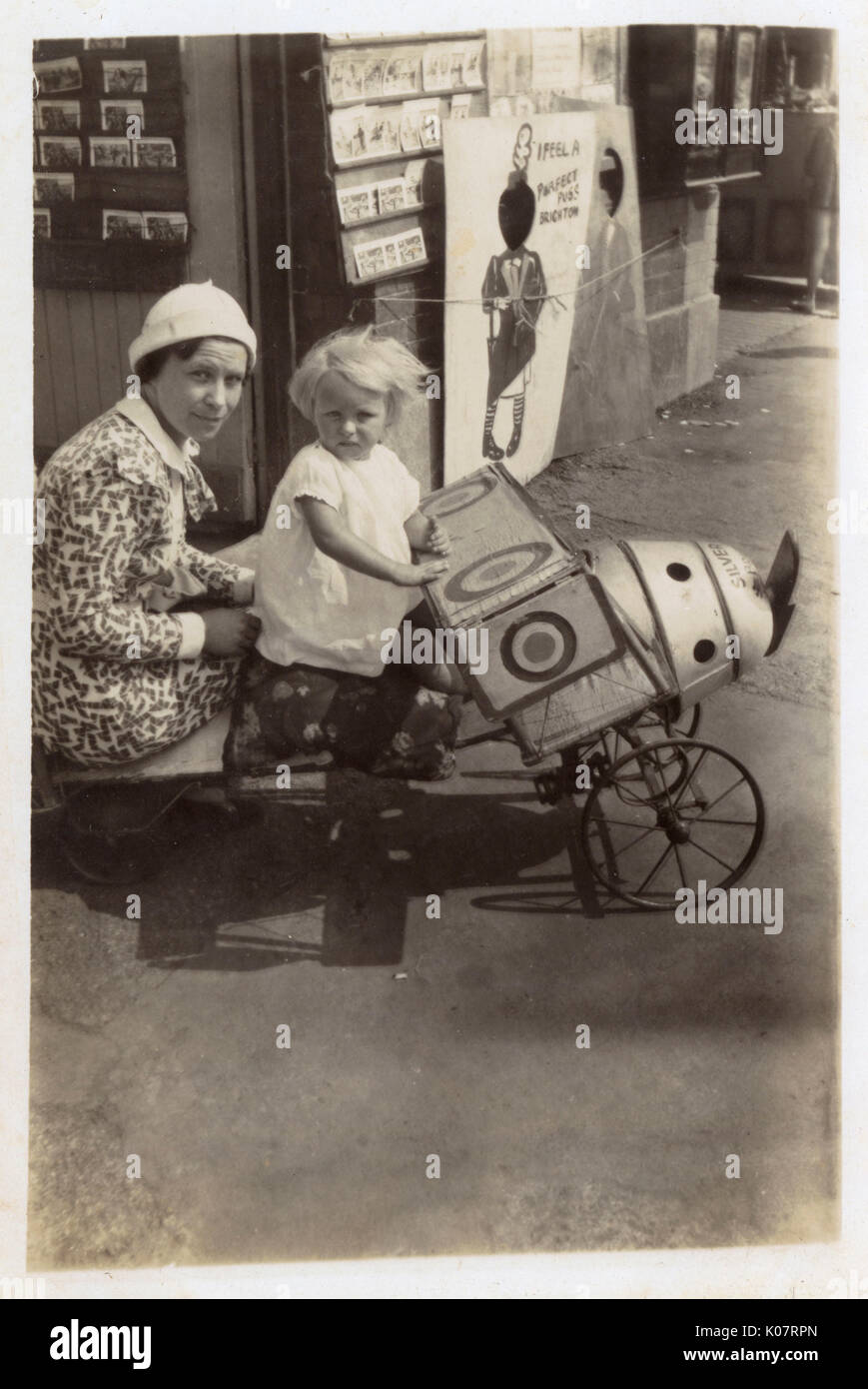 A pin-sharp candid photograph (reproduced on a postcard) showing a Mother and daughter posing in a toy aeroplane (with RAF insignia) outside a photographic shop in Brighton, East Sussex. In the background against the front of the shop are two boards for Children to be photographed behind, with holes cut out for their heads. One bears the slogan: ';I feel a Perfect Puss, Brighton';.     Date: circa 1930 - Stock Image