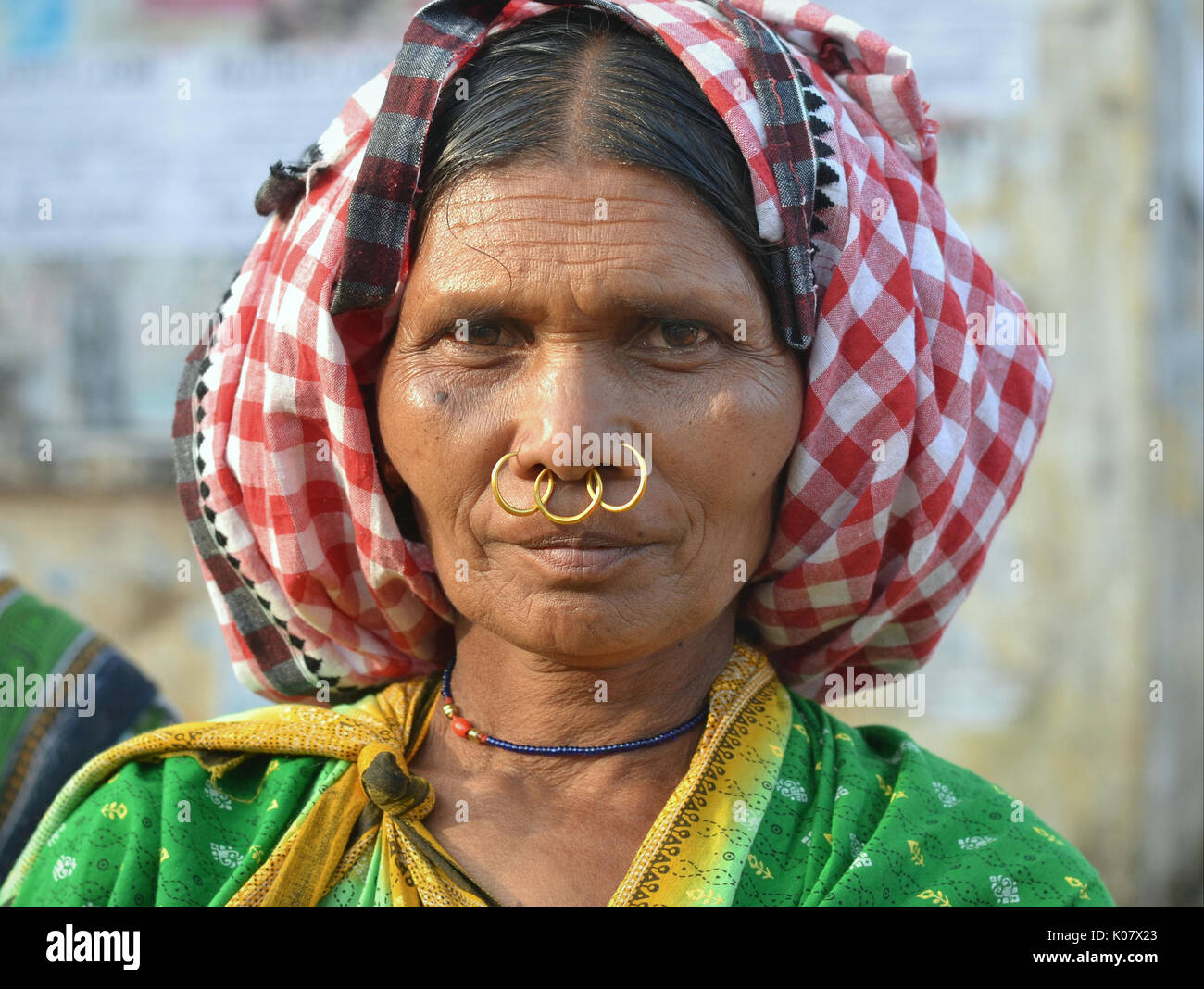 Elderly Indian Adivasi market woman with three golden nose rings. - Stock Image
