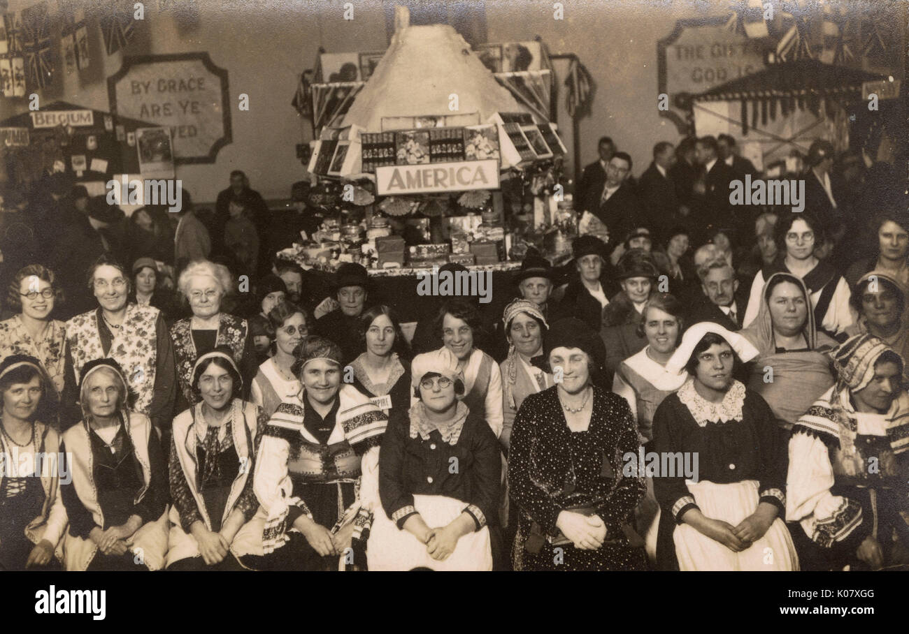 Group of women in national costume, and others in everyday costume, in a church hall, possibly in Harlesden, NW - Stock Image