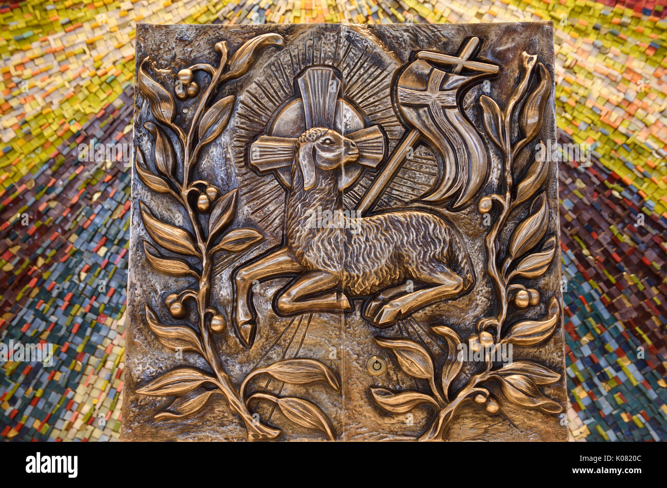 Bronze bas relief doors of Tabernacle in front of mosaic in Catholic church of Lamb of God Agnus Dei with vexillum cross flag and fruit vine - Stock Image