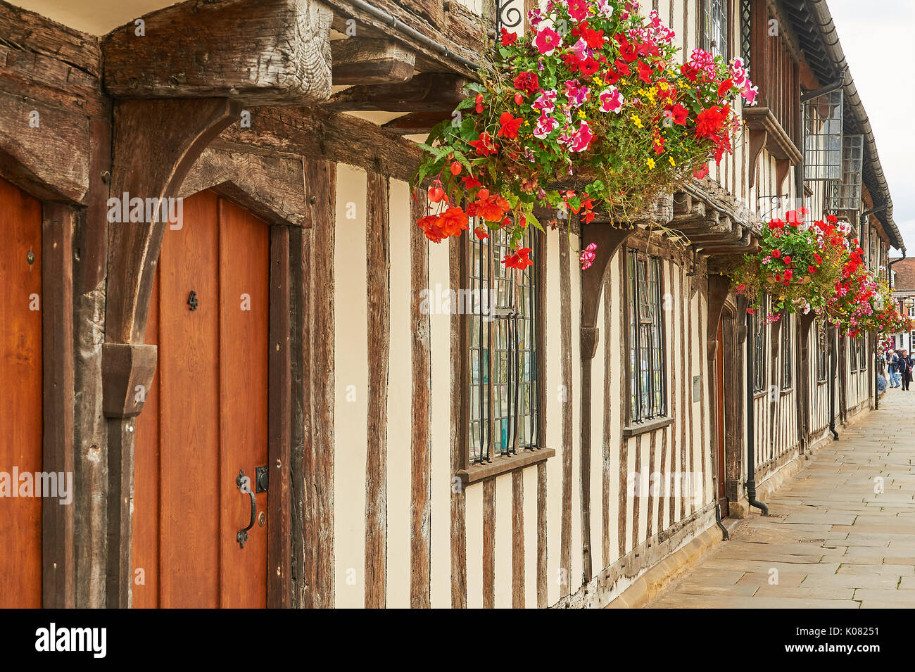 Half timbered almshouses decked out with colourful hanging baskets in Stratford upon Avon Stock Photo