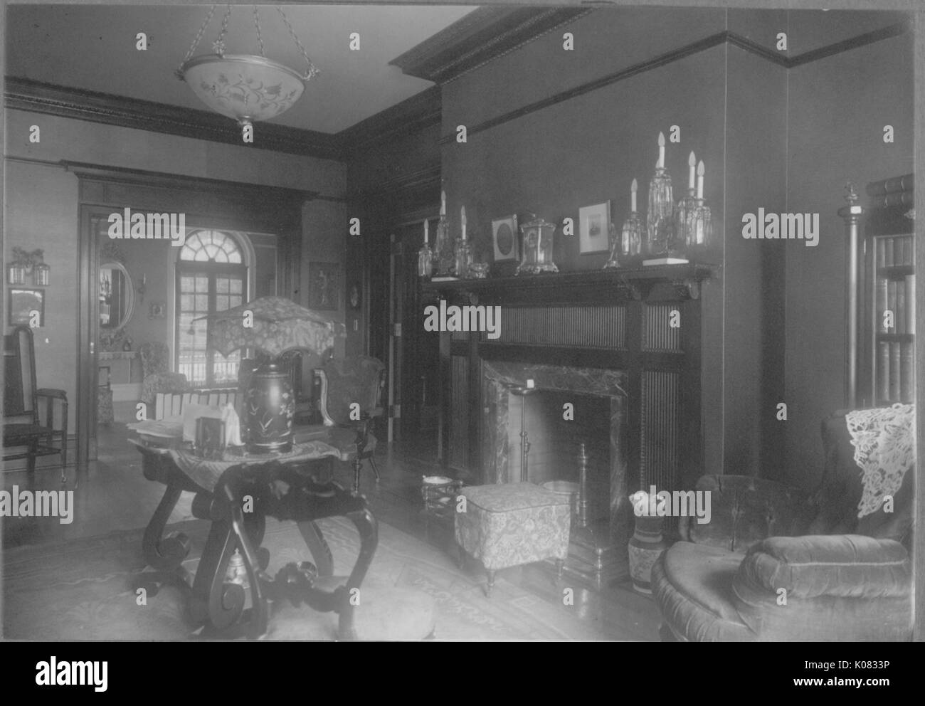 Sitting area of a house with an decorated ceiling lamp, mantelpiece with various candle-holders, a decorative ottoman in front of the fireplace, a wooden able with a lamp in the center of the room sitting atop a carpet, an armchair with a lace overthrow; Roland Park/Guilford, 1910. This image is from a series documenting the construction and sale of homes in the Roland Park/Guilford neighborhood of Baltimore, a streetcar suburb and one of the first planned communities in the United States. - Stock Image
