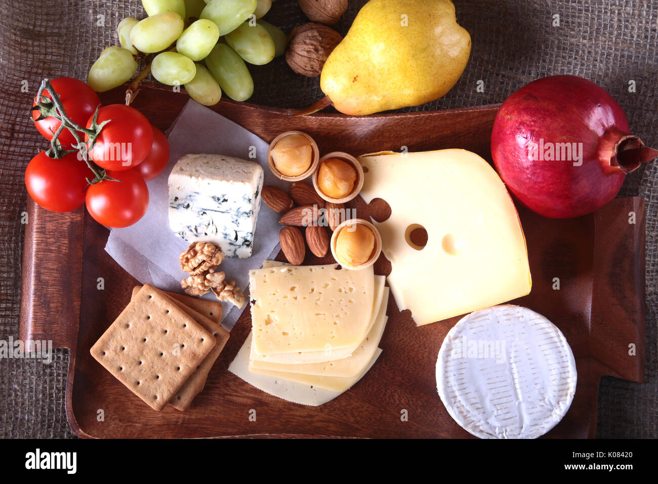 Assortment of cheese with fruits, grapes and nuts on a wooden serving tray. - Stock Image