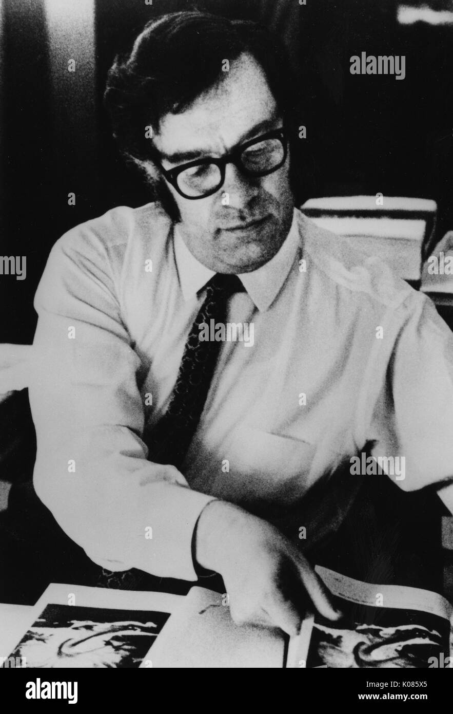 Half-length portrait of author Isaac Asimov, wearing a white shirt, sitting over a table, flipping through pages of a book, wearing glasses and a patterned tie, with a serious facial expression, 1970. - Stock Image
