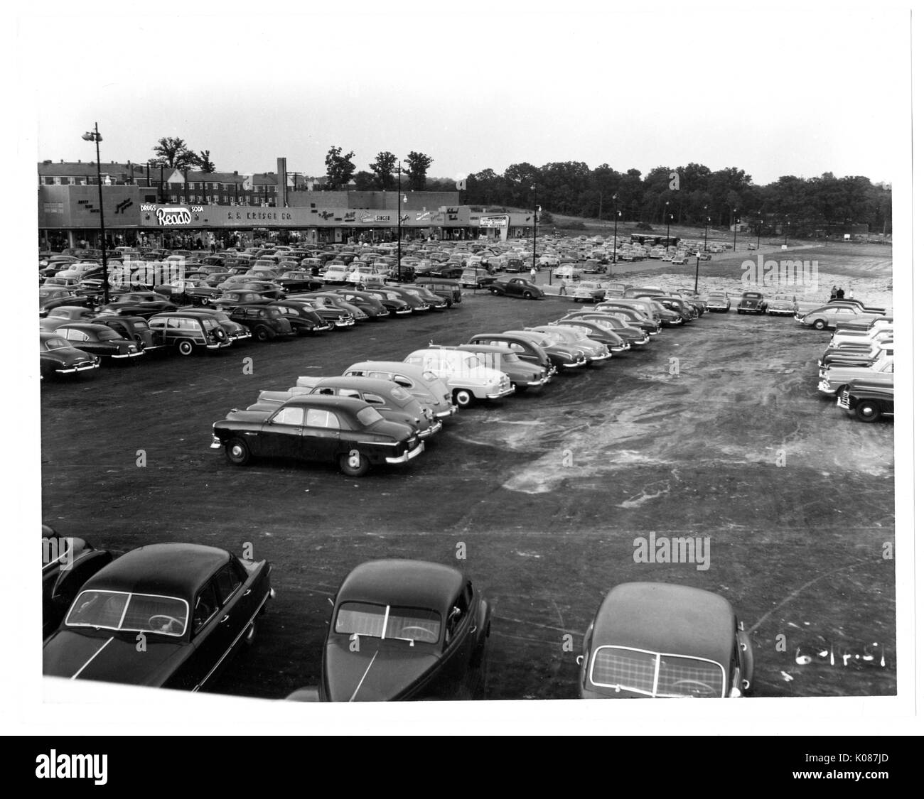 Parking lot of Northwood Shopping center, lots of parked cars, parking lot next to stores as Reads, trees and streetlights also in background, Baltimore, Maryland, 1950. - Stock Image