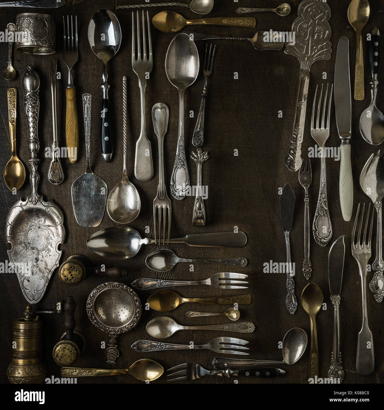 Cutlery, forks, spoons, and knives on dark wooden background - Stock Image