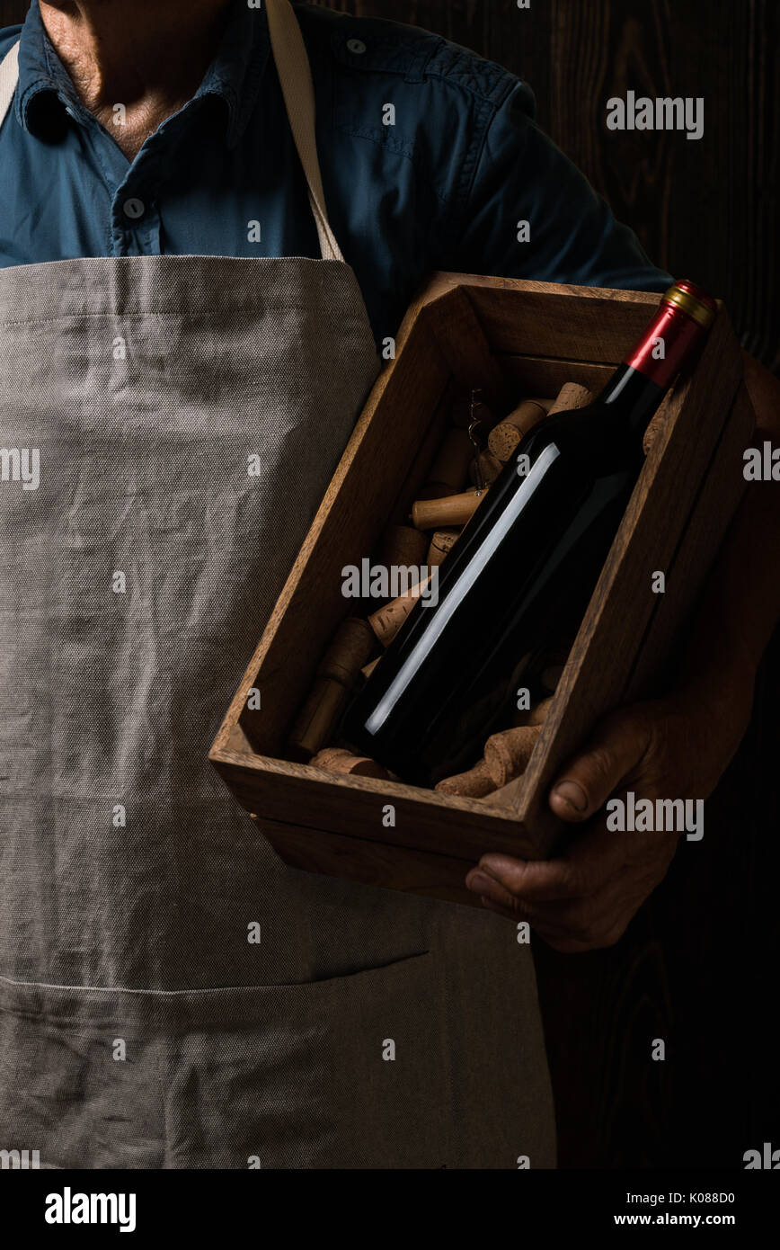 Old winemaker holding a wooden box with bottle of red wine - Stock Image