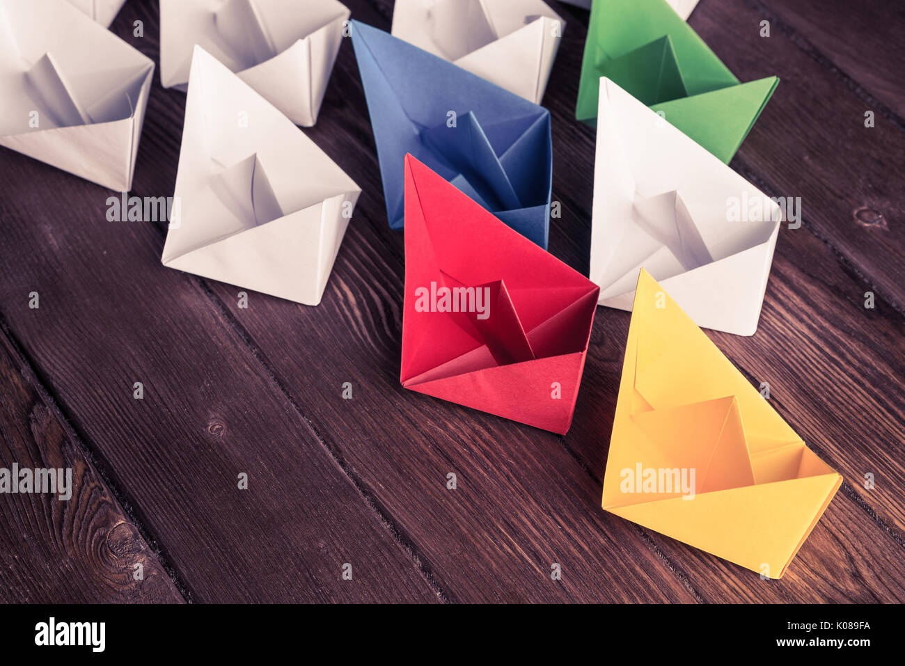 Business leadership concept with white and color paper boats on  - Stock Image