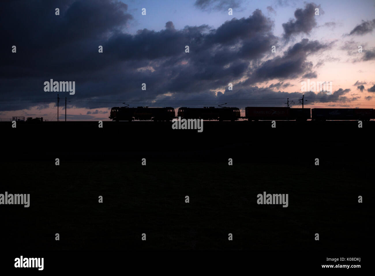 2 Freightliner class 86 electric locomotives making a sillhouette at sun set  with a intermodal (container) freight train - Stock Image