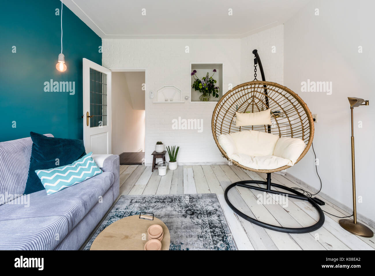 Cozy Living Room With Hanging Chair And Sofa Stock Photo