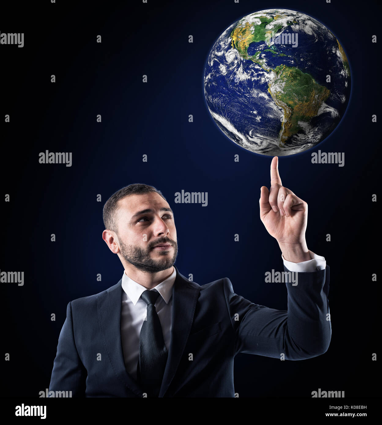 Businessman holds the world with a finger. World provided by NASA - Stock Image