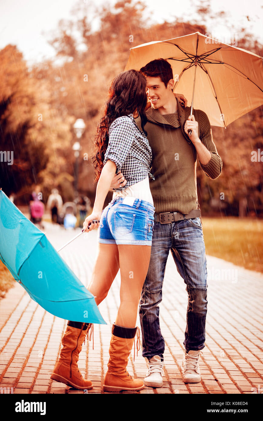 Beautiful Lovely Couple Enjoying And Dancing With Umbrellas In The