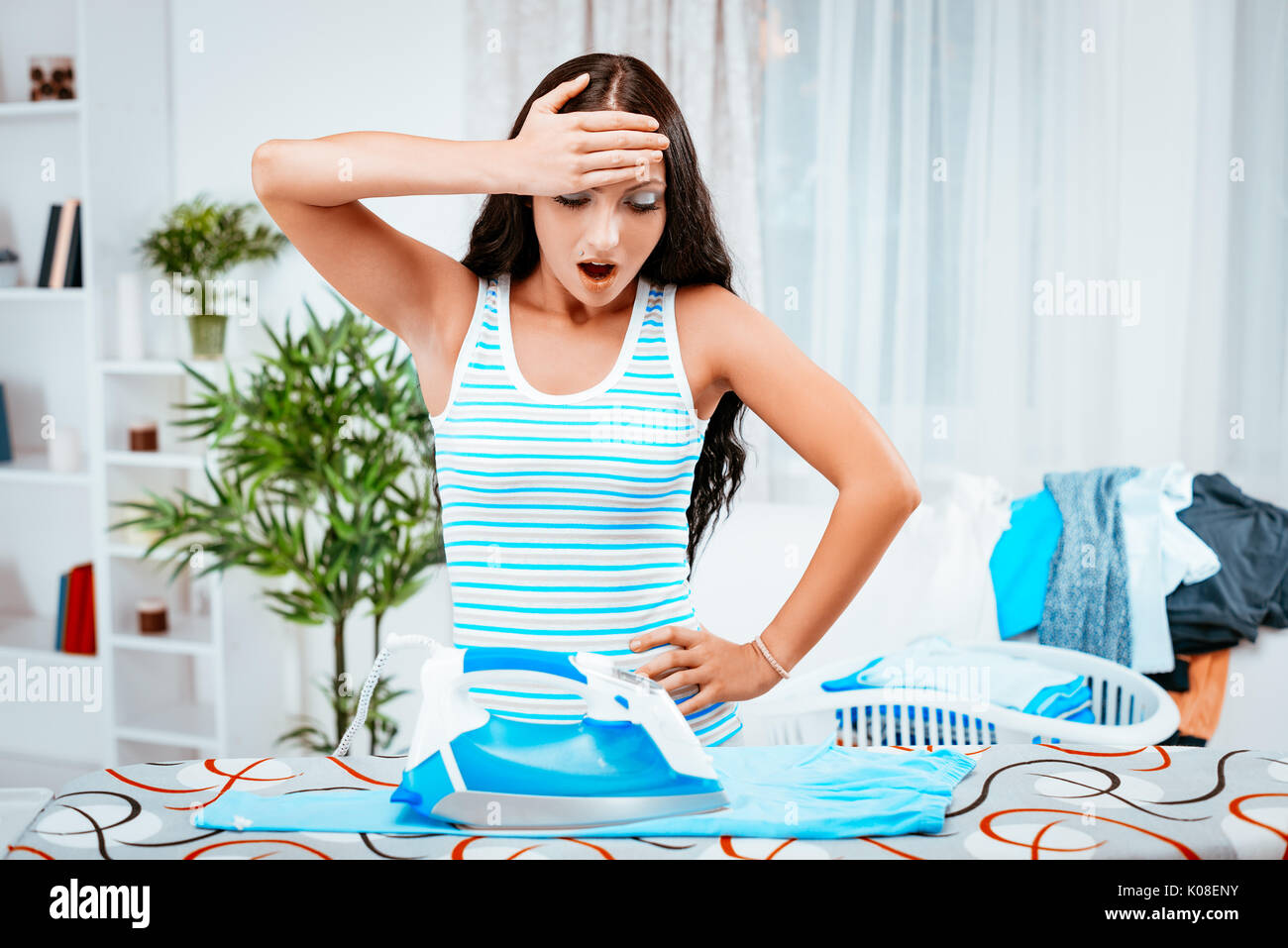 Worried young housewife ironing clothes. - Stock Image