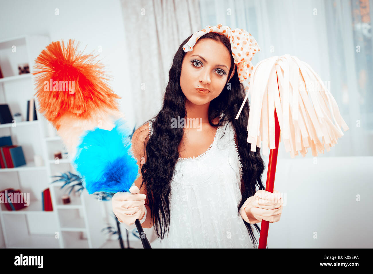 Portrait of a bored young housewife holding a cleaning equipment. Looking at camera. - Stock Image