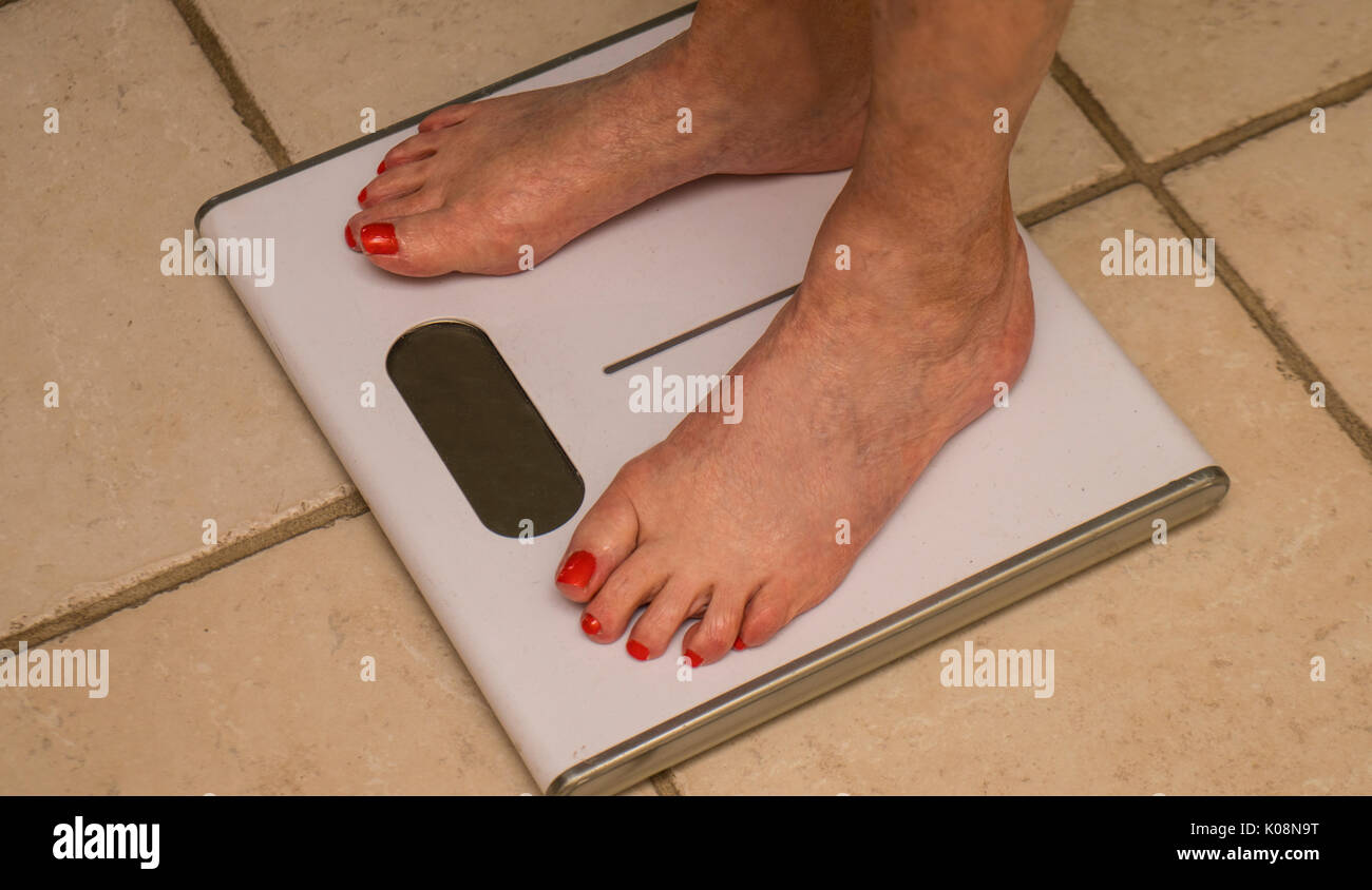 elderly woman standing barefoot  on a bathroom scale and measuring her weight - Stock Image
