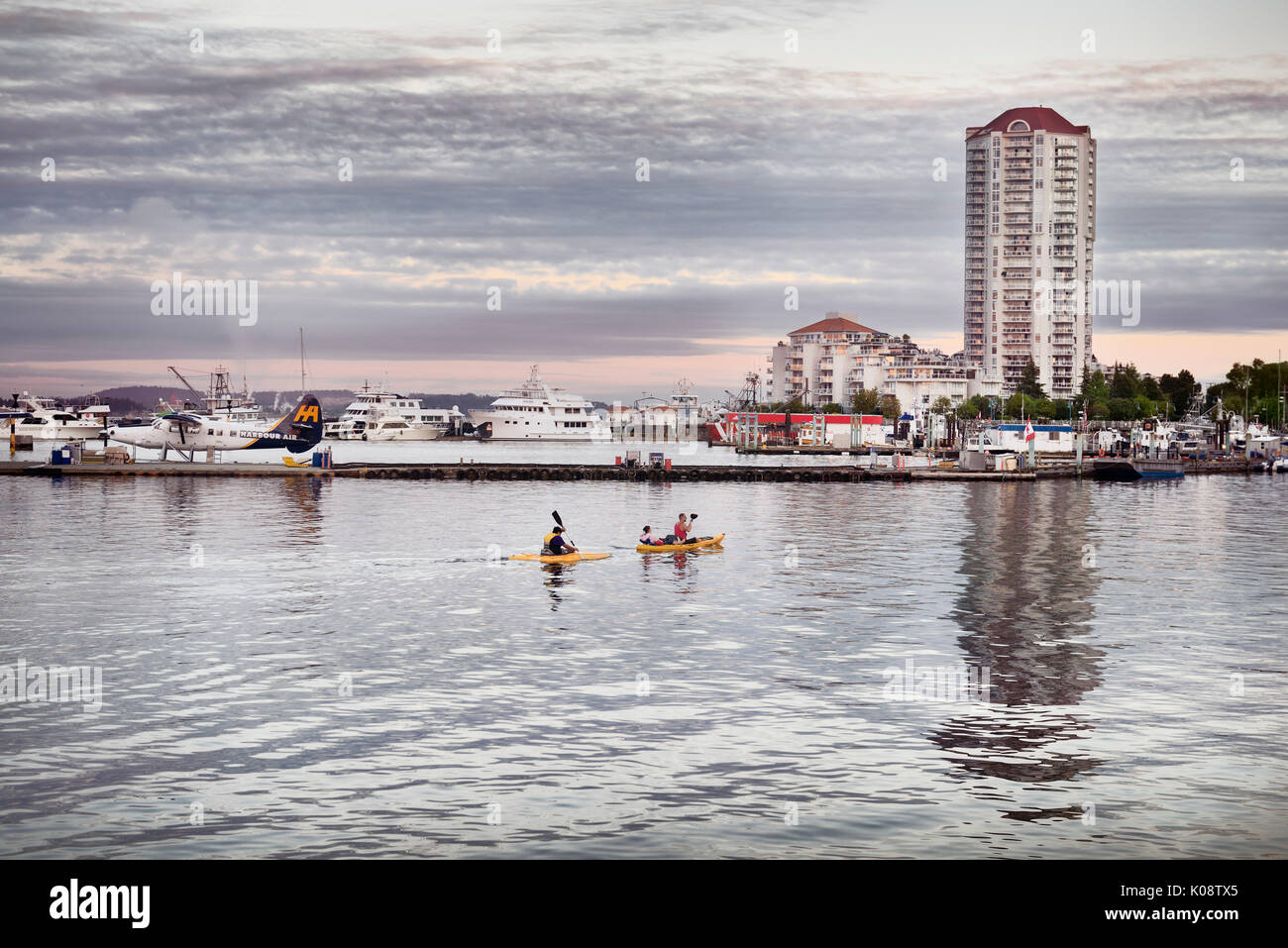 Scenery of people kayaking at Nanaimo city waterfront in the eveninng with the harbour and the city skyline in the background. Vancouver Island, Briti - Stock Image
