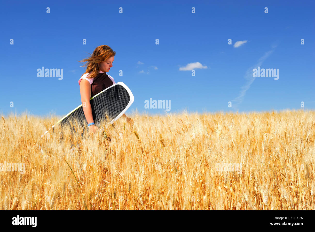 Pretty Girl in Durum Wheat Field, holding wakeboard. - Stock Image