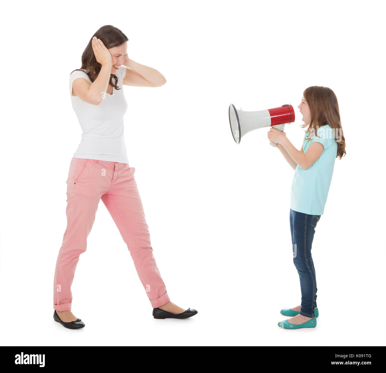 Full length of angry daughter shouting through megaphone at mother against white background - Stock Image