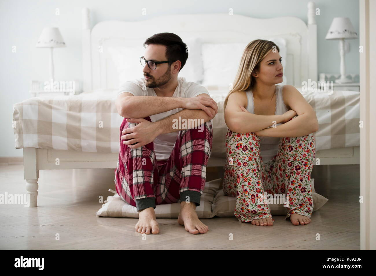 Unhappy young couple having difficulties in relationship - Stock Image