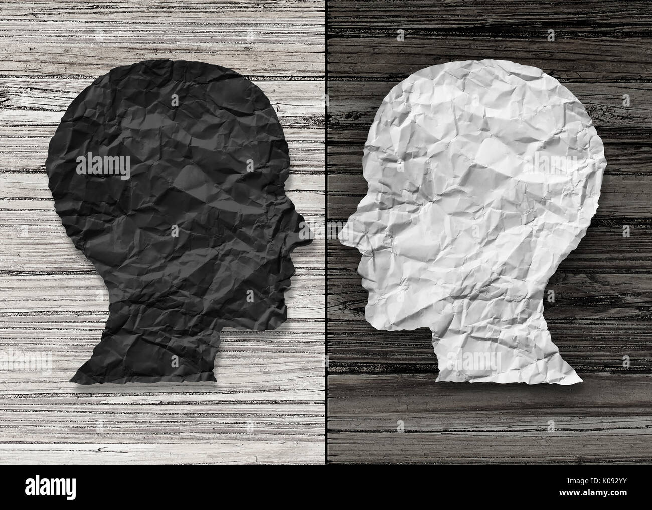 Bipolar mental health and brain disorder concept as a human head in paper divided in two colors as a neurological mood and emotion symbol. - Stock Image