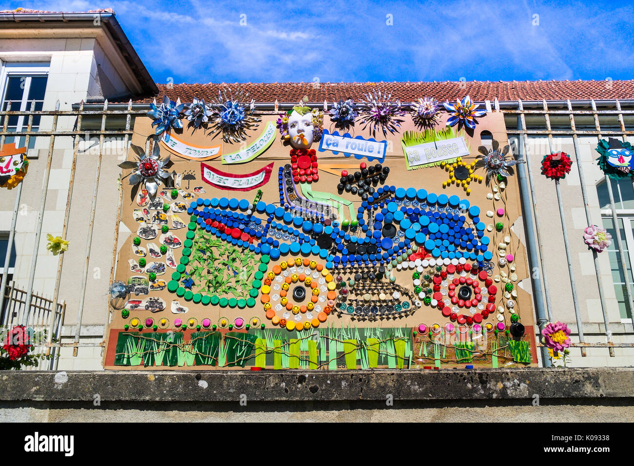 Motor mower picture / collage made by schoolchildren from recycled bottle tops, France. - Stock Image