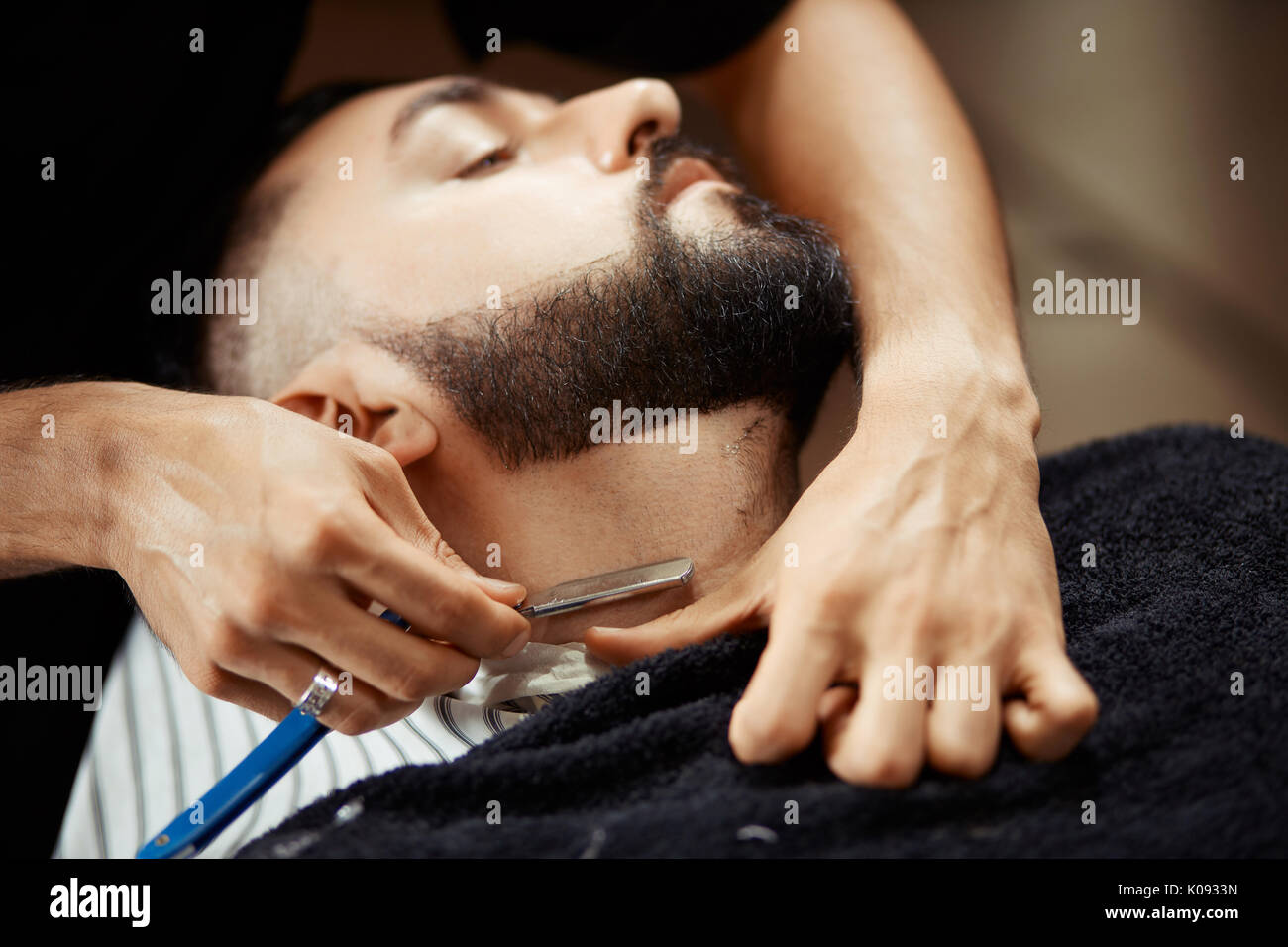 Anonymous man shaving client - Stock Image