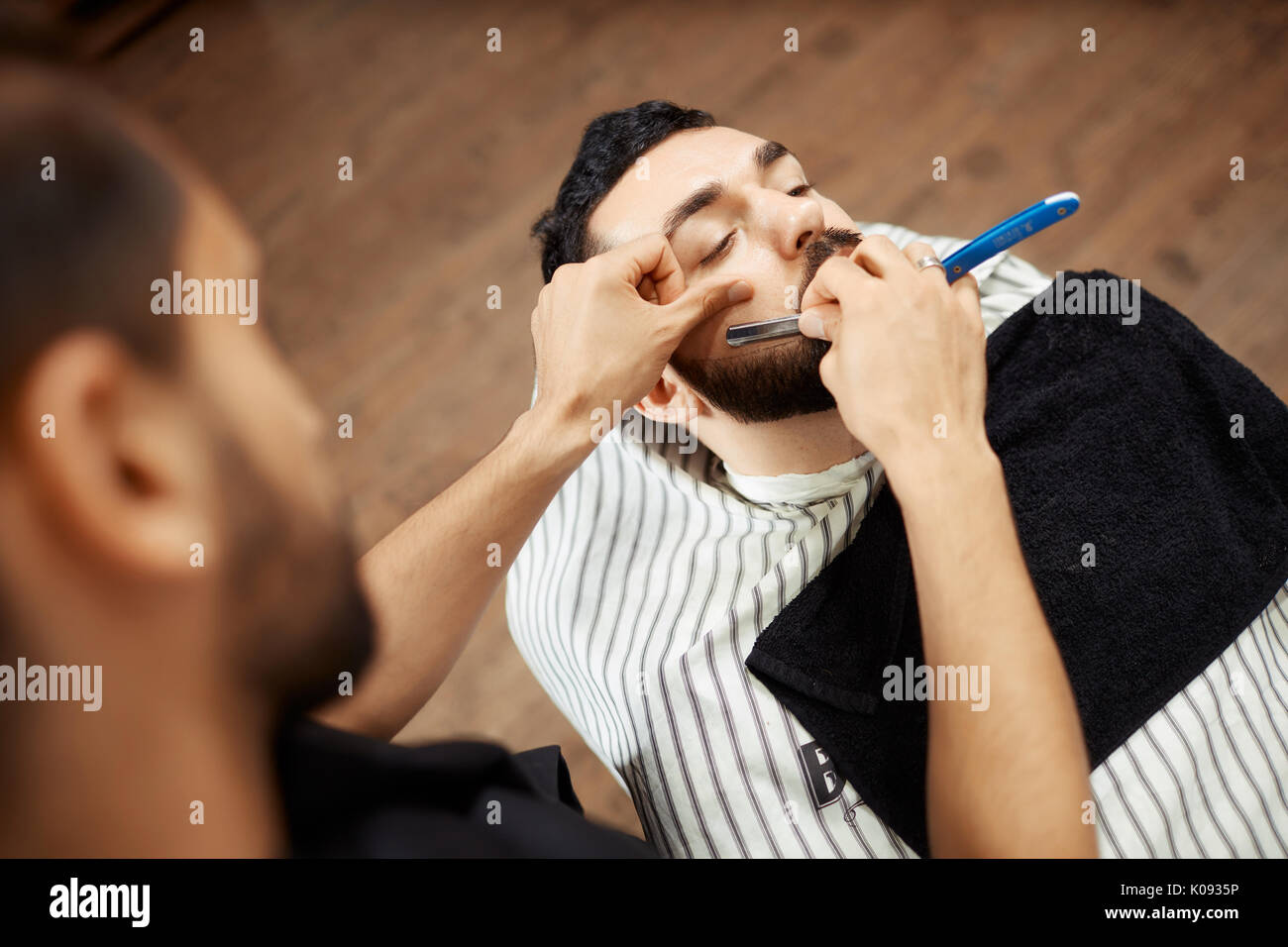 Professional shaving man in chair - Stock Image