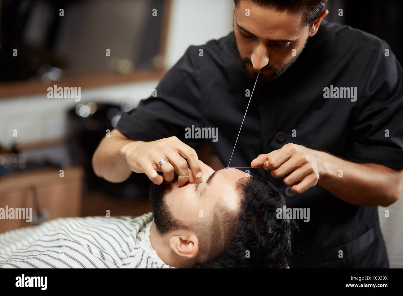 Barber grooming young man in chair - Stock Image