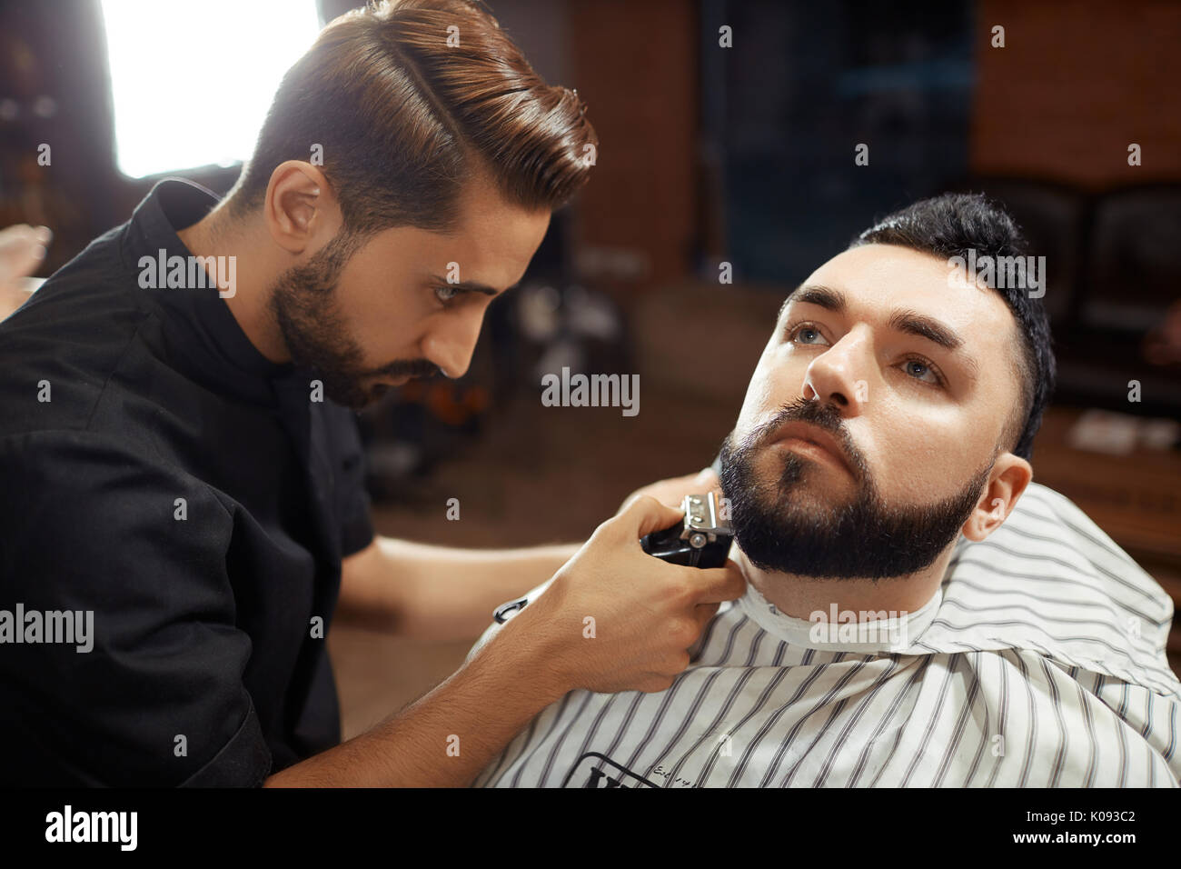 Stylish barber shaving man  - Stock Image