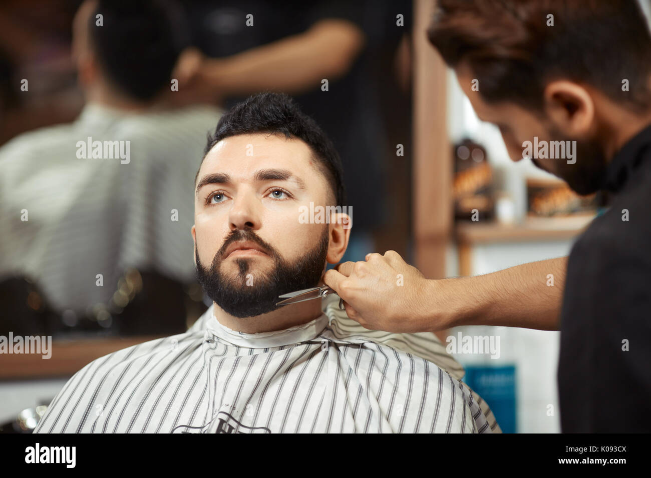 Barber grooming man in chair - Stock Image