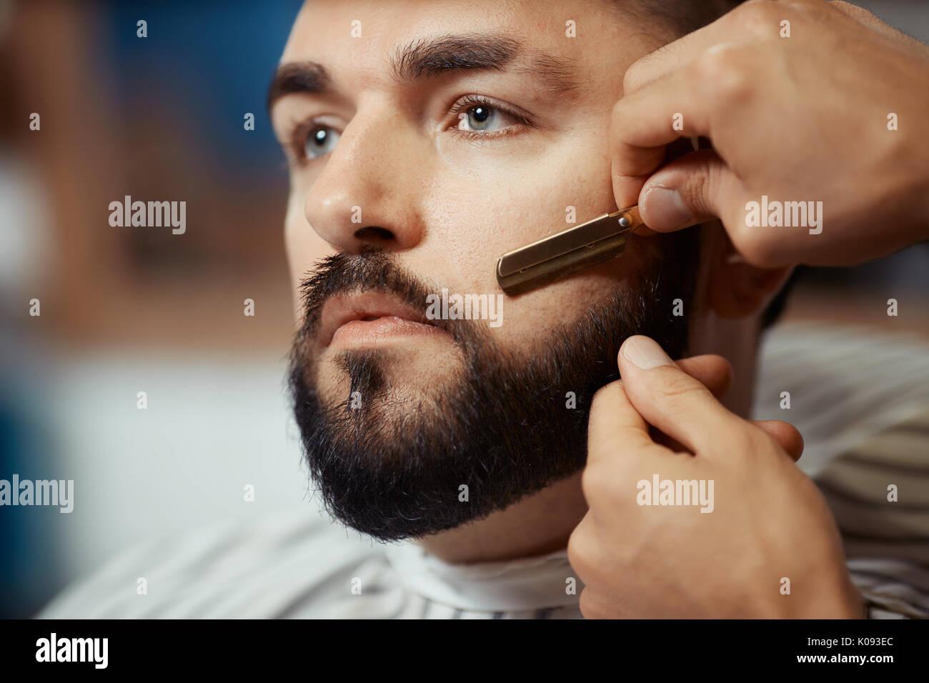 Crop man trimming beard of client - Stock Image